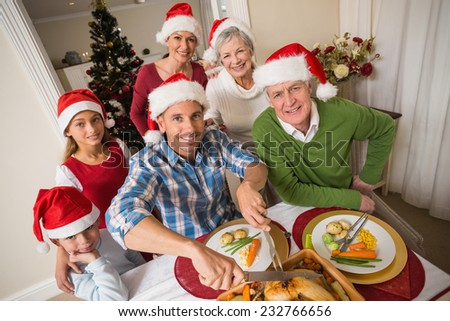 Father in santa hat carving chicken at christmas dinner at home in the living room - stock photo