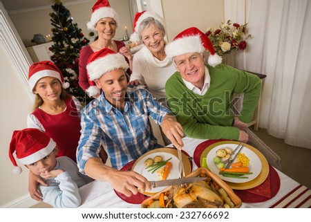Father in santa hat carving chicken during christmas dinner at home in the living room - stock photo