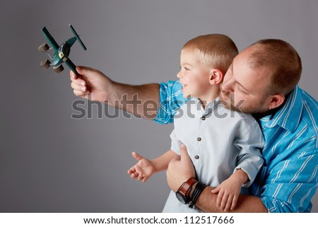 father in thirties and toddler boy of three years old play with airplane toy on studio background - stock photo
