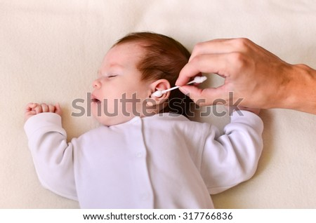 Father is cleaning baby's ear