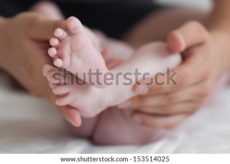 Father is gently holding his baby feet