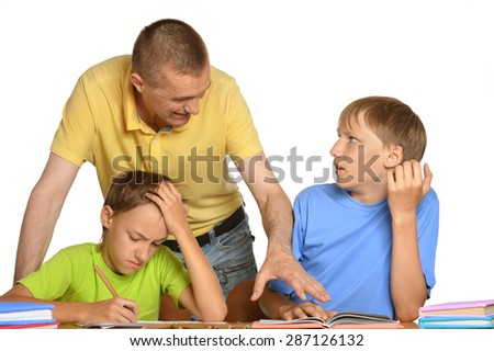 Father is helping his kids with their homework - stock photo