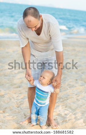 Father is helping his son to make first steps outdoor - stock photo