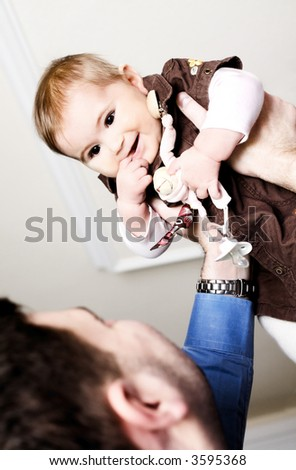 Father is lifting his baby girl, indoor.