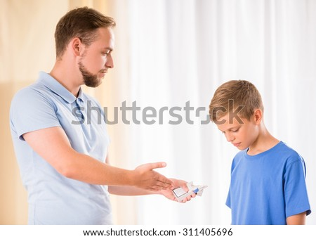 Father is showing a cigarettes to his son. - stock photo