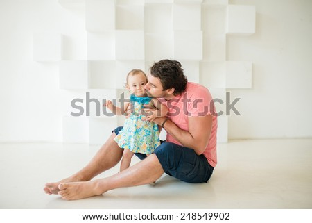 father kissing beautiful little girl on a white background - stock photo