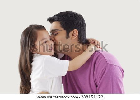 Father kissing daughter on cheeks - stock photo