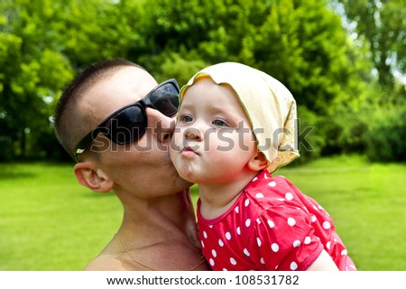 Father kissing his baby outdoor - stock photo