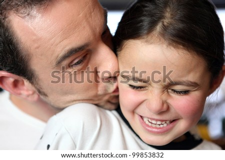 Father kissing his daughter - stock photo