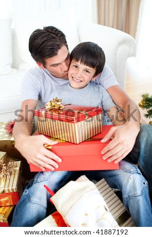 Father kissing his son after giving him a Christmas gift in the living-room - stock photo