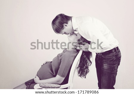 father kissing pregnant mother - stock photo