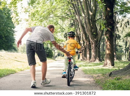 Father learn his little son to ride a bicycle - stock photo