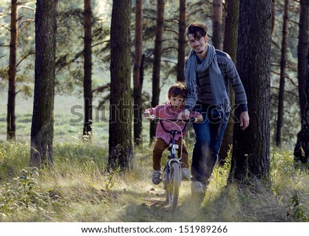 father learning his son to ride on bicycle outside - stock photo