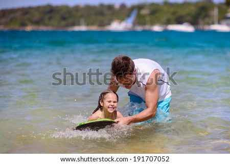 Father learning kid to swim with a board at sea