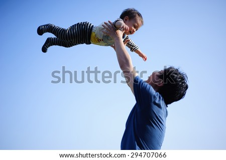 father lift his baby isolated on blue sky