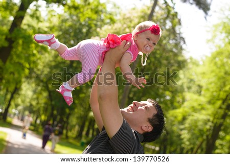 Father lifting baby girl above head - stock photo