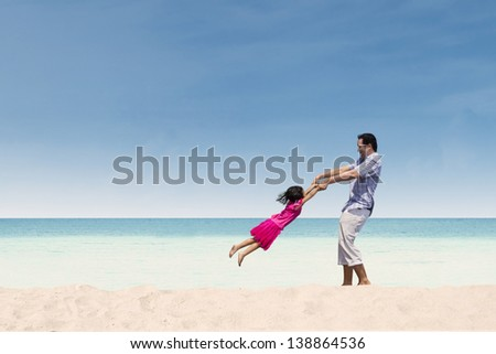 Father lifting her daughter on the beach - stock photo