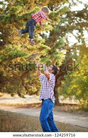 Father lying on grass smiling as son climbs on his back and hugs his neck - Summer holidays - stock photo