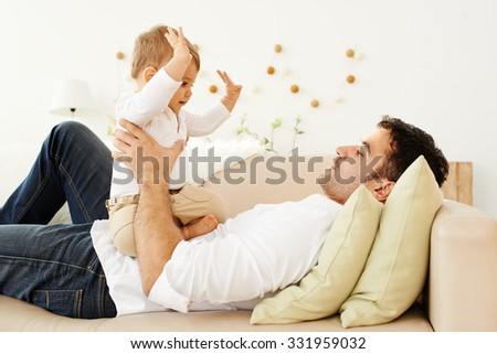 Father lying on the sofa and playing with his little son