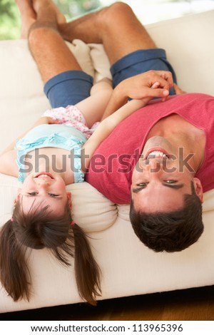 Father Lying Upside Down On Sofa With Daughter - stock photo
