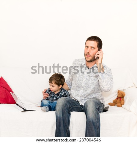 Father making a phone call and taking care of his son playing with tablet on the sofa - stock photo