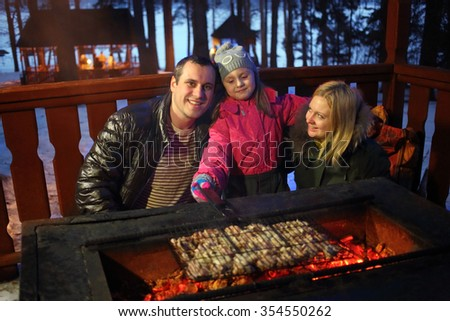 Father, mother and daughter near the brazier with barbecue on a winter evening - stock photo