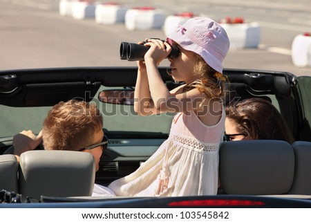 Father, mother and daughter ride in convertible car; pretty girl looks through binoculars - stock photo