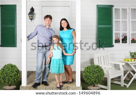 Father, mother and daughter stand on porch of new white house. - stock photo