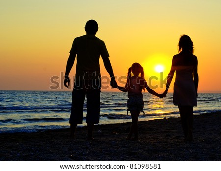 Father, mother and daughter walking on the beach