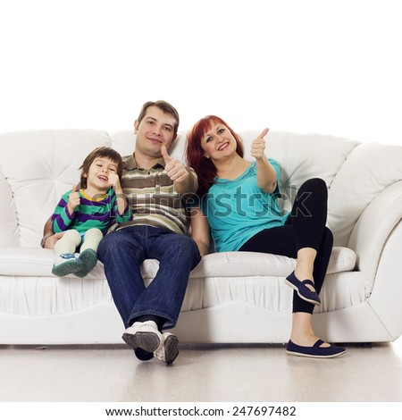 Father, mother and son sitting on the sofa showing hand ok sign over white background - stock photo