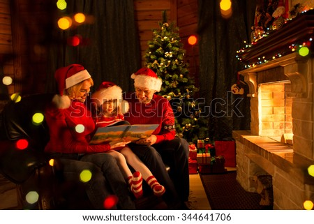 Father, mother and their child read a book by a Christmas tree in cozy living room in winter - stock photo