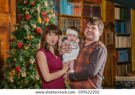 Father, mother and their cute little daughter are ready to celebrate Christmas
