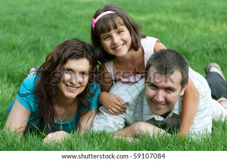 Father, mother and their daughter are lying on the green grass in the summer park