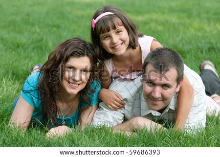 Father, mother and their daughter are lying on the summer green grass
