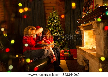 Father, mother and their daughter reading a book by a Christmas tree in cozy living room in winter - stock photo