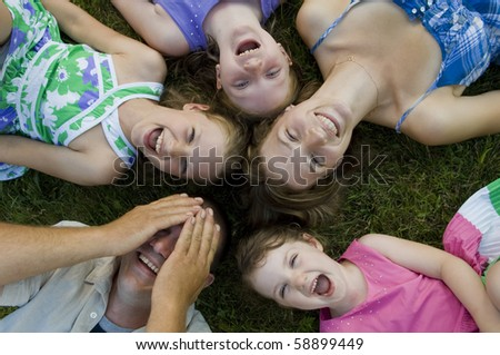 Father, mother and their four daughters have some fun in the backyard. - stock photo