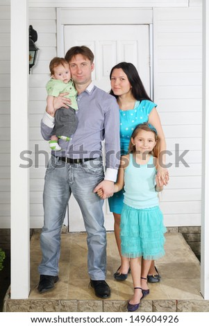 Father, mother, baby and daughter stand on porch of new house. - stock photo