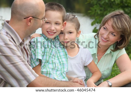 father, mother, little boy and little girl near pond. focus on little girl's face - stock photo