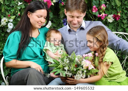 Father, mother, sister and baby look at bunch of flowers on bench in garden near verdant hedge. - stock photo