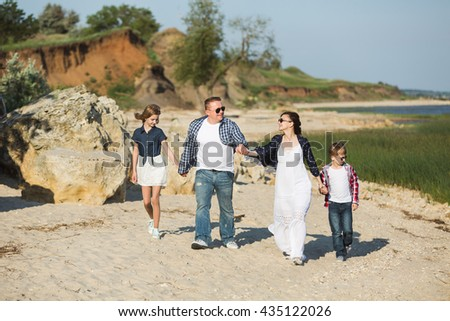 Father, mother, son and daughter walking on the beach. A woman dress in boho style. Sunset.