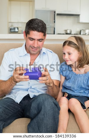 Father opening gift given by daughter while sitting on sofa at home - stock photo