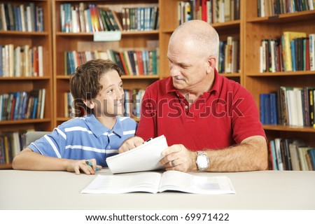 Father or male teacher tutoring a young student in the school library. - stock photo