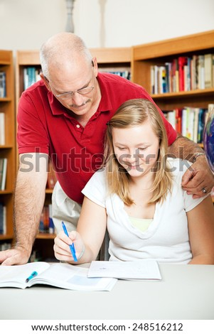Father or teacher helping a teenage student at the library.   - stock photo