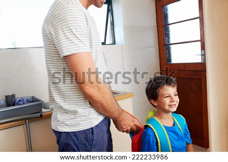 Father packing school lunch into son backpack before he goes to learn - stock photo
