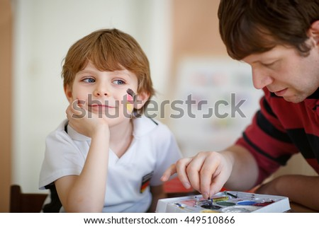 Father painting flag on face of little son for football or soccer game. Kid boy fan happy about game of team in champions league. Selective focus - stock photo