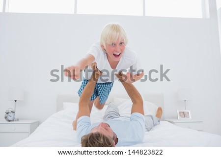 Father playing airplane holding his son in bed - stock photo