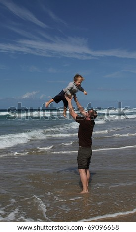 Father playing at the beach with his son - stock photo