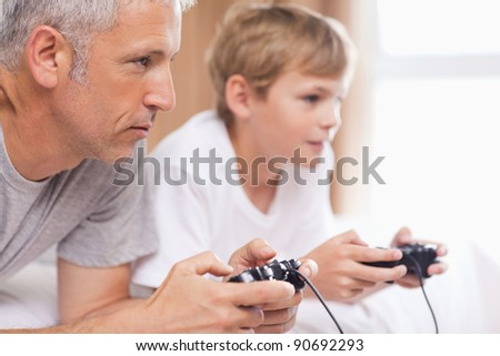 Father playing video games with his son in a bedroom - stock photo