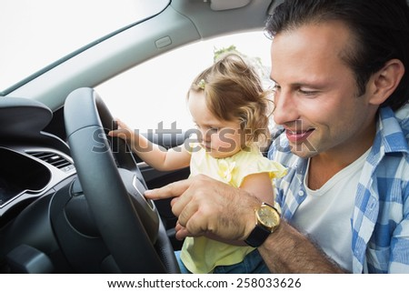 Father playing with baby in drivers seat in his car - stock photo