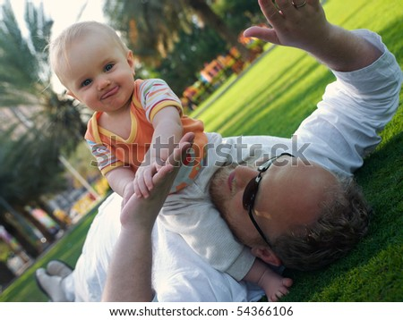 Father playing with child on a lawn - stock photo